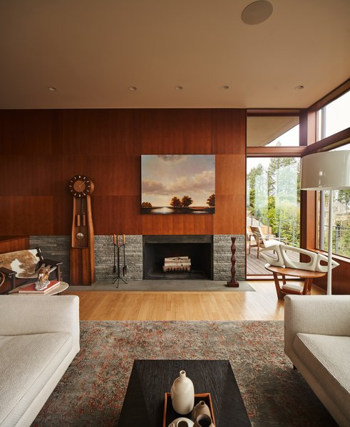 """Many of the windows facing the view were enlarged. Greg and Kirsten opted not to bring in easier-to-maintain aluminum framing. Instead they stuck with Douglas fir, albeit with thinner stocks. """"I definitely felt the gravitational pull towards midcentury,"""" Greg explains. The original fireplace was redone in local basalt to match a pair of new hearths, one upstairs and one on the patio."""