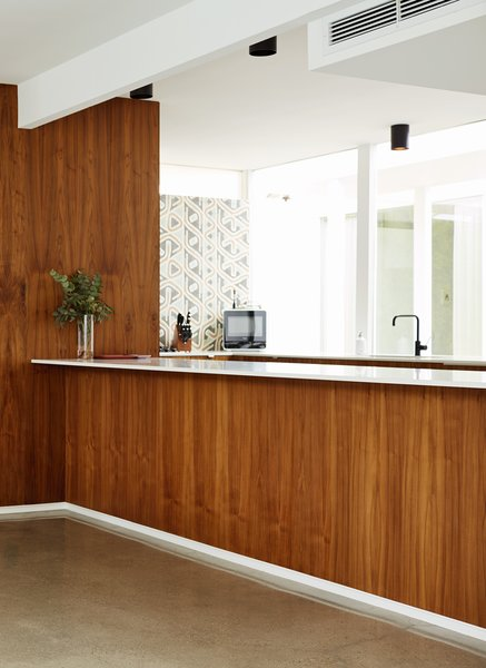 "Jessy and Steve were dismayed to find that the walnut plywood siding in the kitchen and dining area had been painted over. ""You can't strip that out,"" says Jessy, an interior designer. ""We had to replace it."" When they popped off the moldings at the foot of the counter, they discovered original recessed baseboards, which give the kitchen bar the appearance that it is floating."