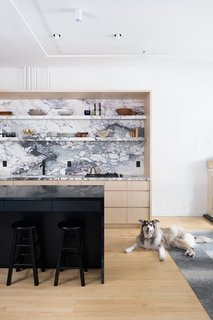 Brandon Dean of Dean Works used two types of stone in the kitchen: a lighter, more active marble for the countertops and backsplash, and a tamer, dark soapstone for the kitchen island.