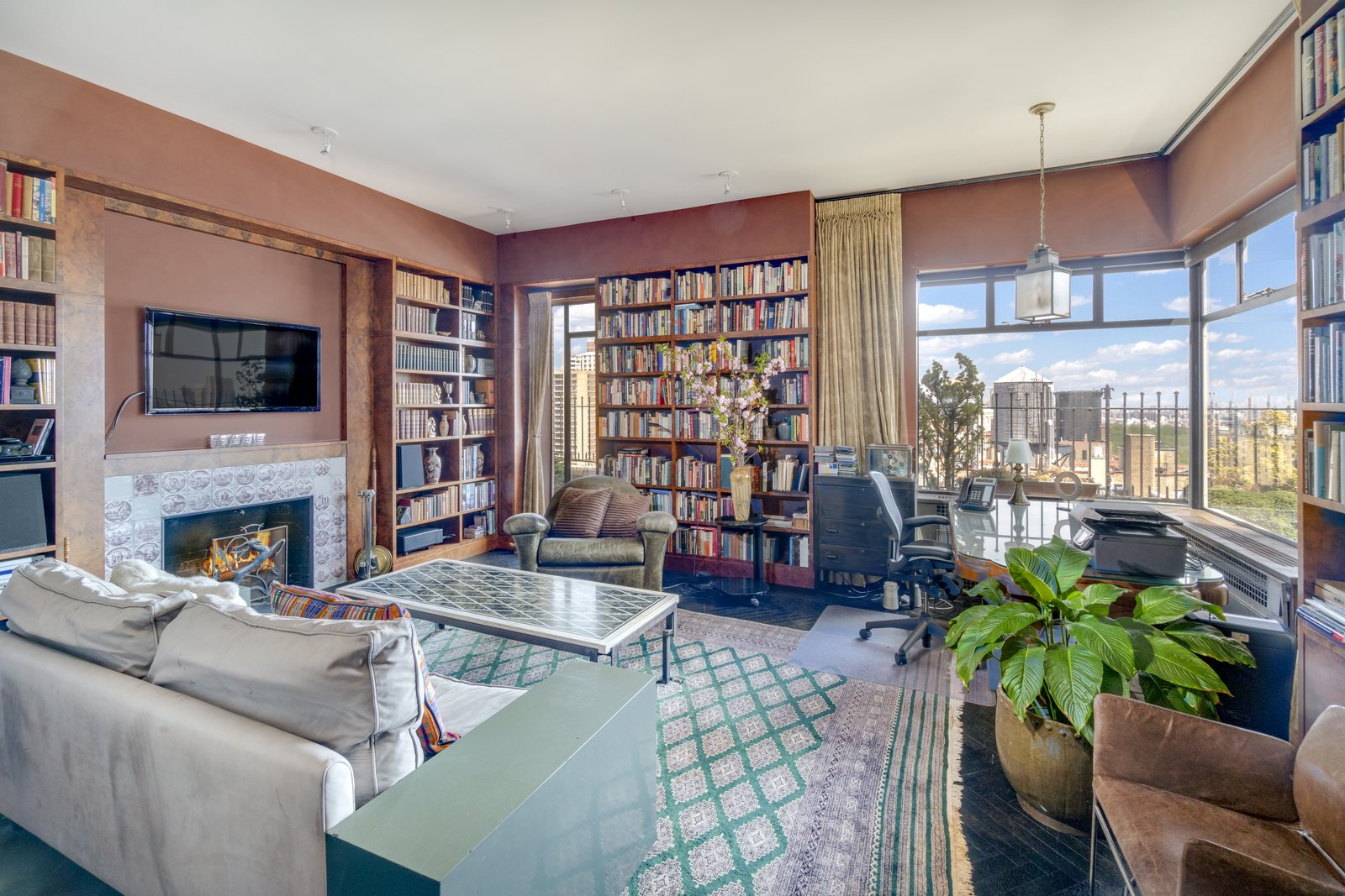 Right off the foyer is an inviting den, which also houses a spectacular corner library. The home's 27 windows allow plenty of sunlight to flood in throughout the space.  Photo 4 of 6 in Barbra Streisand's Former Central Park Penthouse Asks $11.25M