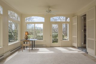 An airy sun room offers warm, natural light and expansive views of the property.