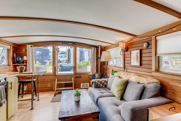 Despite its small size, the houseboat's well-established layout makes efficient use of every square inch inside. With rustic wood-paneling, the home also has plenty of built-in shelving.