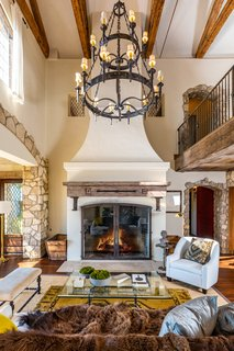 The two-story great room is crowned by a striking chandelier.