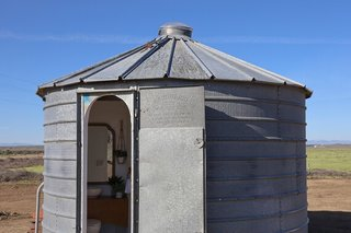 The bathroom is located in a converted silo, sited right next to the potato.