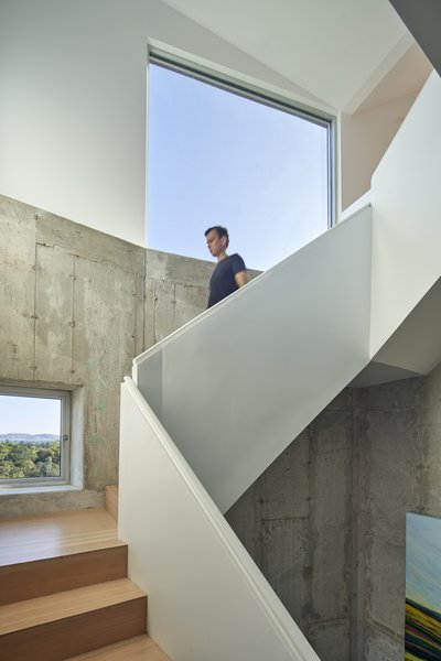 A staircase guides visitors from the home's entry in the rough cement base to the bright and airy residential space.