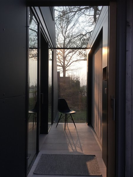 After passing through the wooden opening, guests enter the home via a glass-encased hallway.