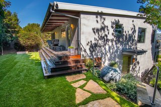 Offering plenty of privacy, the backyard also comes with a lush, grassy lawn.