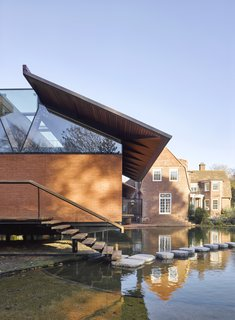 A brick facade on one of the structures relates the new buildings to the existing home, and creates the impression of a monolithic form floating effortlessly above the water.