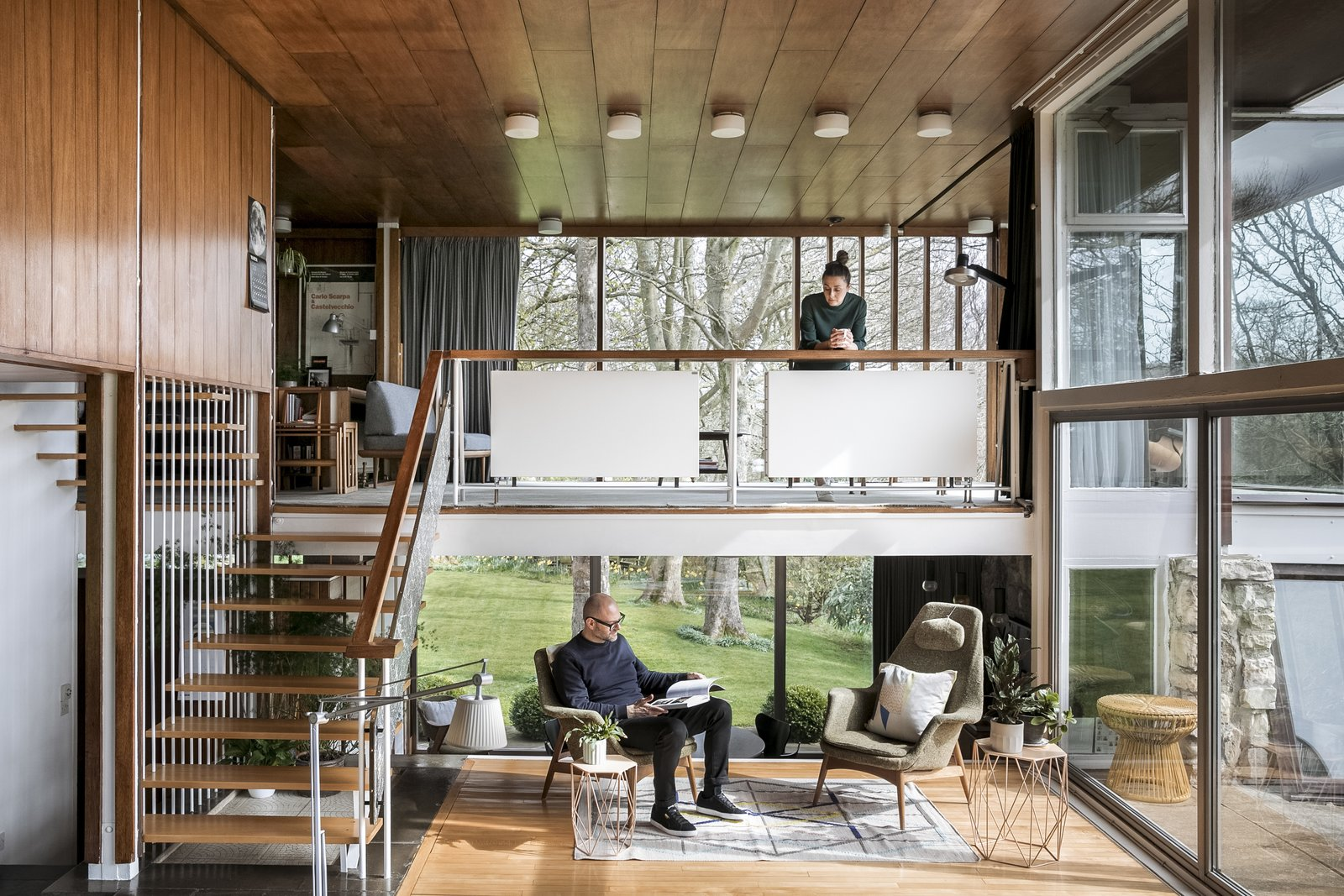 The couple purchased the living room's H.W. Klein chairs with the house. Another existing piece was the mezzanine's daybed, designed by Peter Hvidt and Orlando Mølgaard Nielsen. An original floating staircase leads to the mezzanine and then up to the second floor. The open, straight-forward spaces speak to one of Christian's guiding principles: