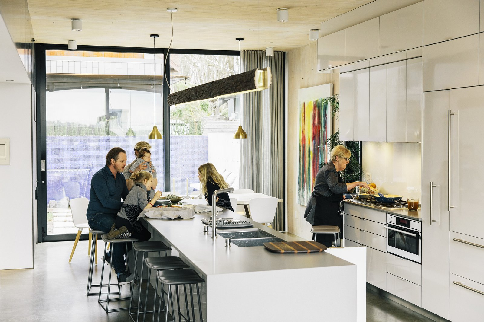 Kitchen, Concrete, Drop In, White, Concrete, Concrete, and Ceiling With an eye to making the home eco-friendly, both structures were built of prefabricated cross-laminated timber, while large openings, like the sliders in the kitchen, promote cross-ventilation.  Best Kitchen Ceiling Concrete Concrete Photos from A Vancouver House Connects a Family