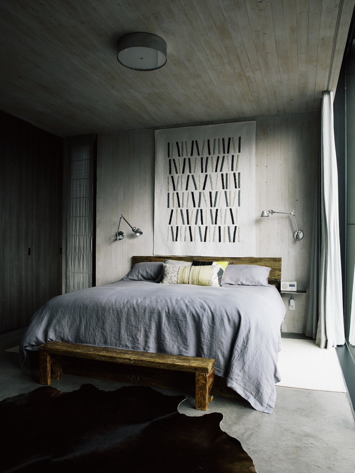 Bedroom, Wall, Concrete, Bed, and Ceiling Karen and Stephen made their bed using wood from an old weathered deck. A quilt by Karen hangs above it. The wall lamps are by Artemide, the bedcover is from North Shore Linens, and the antique bench is from China.  Best Bedroom Concrete Bed Photos from A Vancouver House Connects a Family