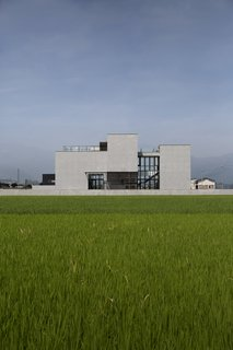 The home's concrete walls stand out among the bright green rice paddies.