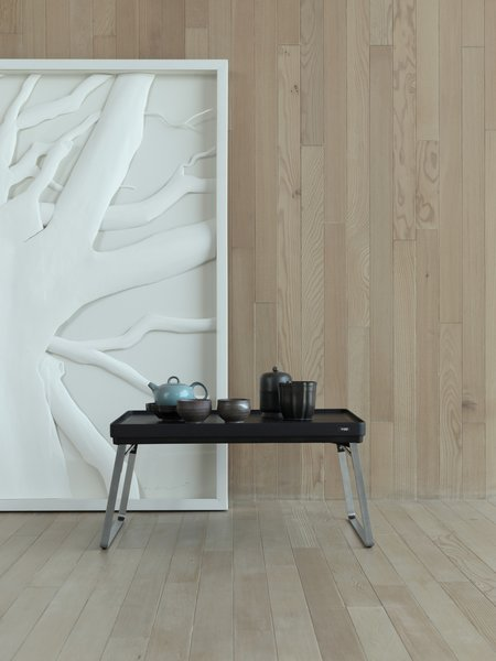 Artwork by Lue Chantorn stands behind a low black mini-table from Vipp.