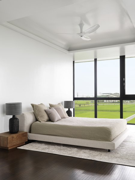Floor-to-ceiling windows open the master bedroom to panoramic views. Flanking a bed from Living Divani are bedside tables and lamps from Originals Furniture Singapore. The flooring is stained oak.