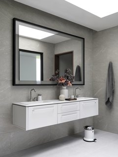 In the master bath, the floating vanity and pedal bin are from Vipp; the mirror was designed by André.