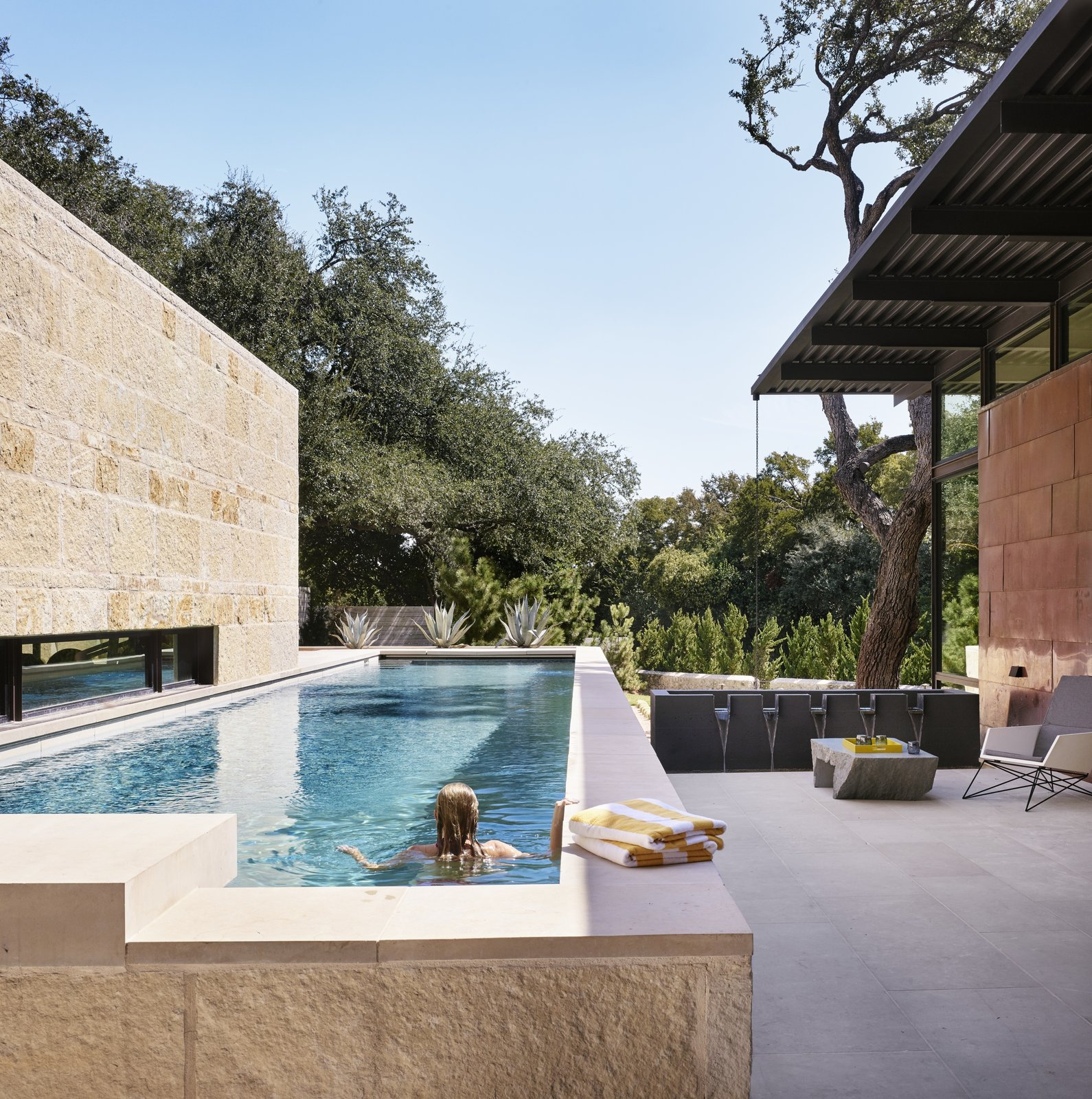 """Outdoor, Lap, Hardscapes, Shrubs, Landscape, Horizontal, Swimming, Trees, Small, Concrete, Back Yard, Small, Hanging, and Stone Throughout the day, light animates the limestone walls to various effects. """"As the sun rotates around and is more oblique to the texture of the stone, it casts these wonderful shadows on it,"""" says Raike. """"And you just get a real appreciation for the texture of the stone and the richness of the colors in it.""""  Best Outdoor Photos from RM-3 Episode Five: Clams"""