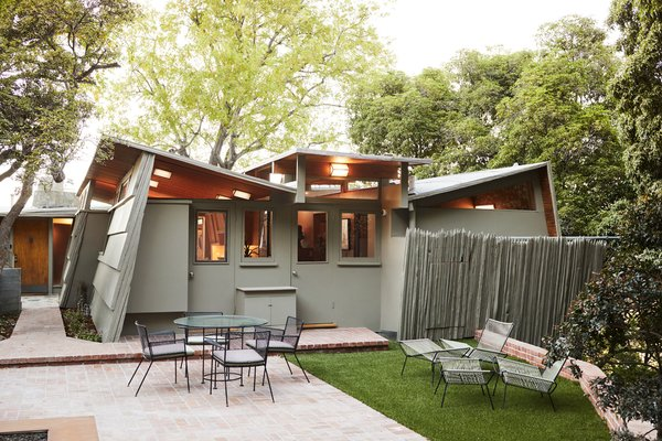 The Kallis House is known for its butterfly roof, which enabled Schindler to add clerestory windows to bring in more light. For the exterior paint, the couple ordered a custom color from Behr.