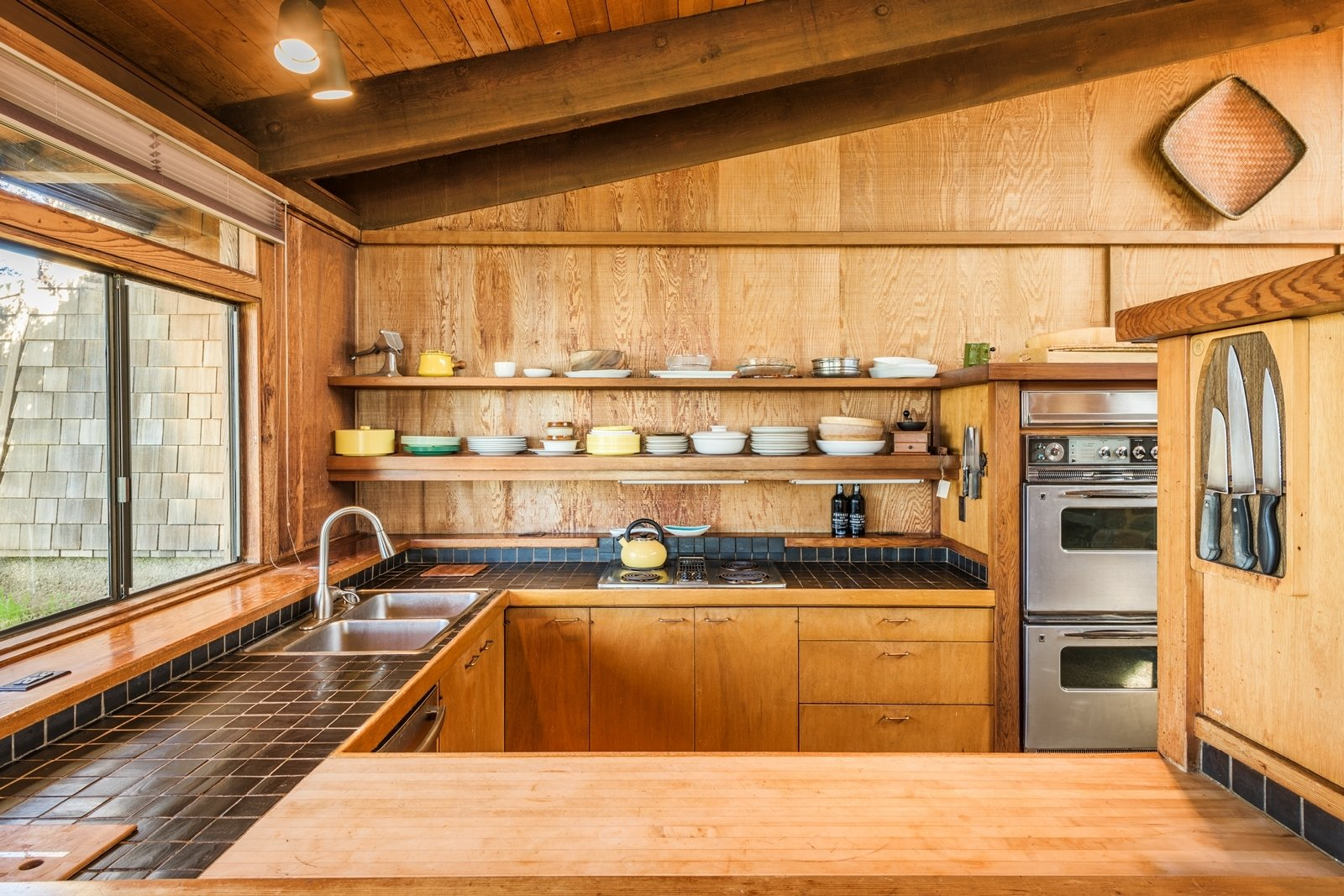 Kitchen, Drop In, Cooktops, Wall Oven, Tile, and Ceiling Comprised of beautiful wood cabinetry and open shelving, the kitchen also has a double-oven.  Best Kitchen Cooktops Drop In Wall Oven Ceiling Photos from A Sea Ranch Stunner With a Green Roof Asks $1.3M