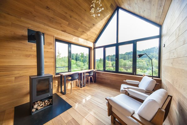 Oiled oak was used for the cladding of the walls, ceiling, floor, and built-in furniture. The gabled windows and expansive glazing allow natural light to flood throughout.