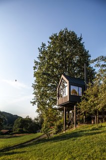 Framing picturesque views of a small valley and nearby orchard, the tree house is comprised of a steel frame with four wooden support beams.
