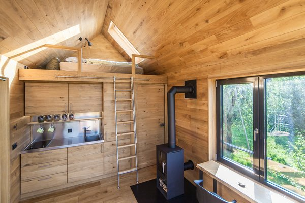 Above the integrated pantry and bathroom is a lofted sleeping area. A small wood stove creates warmth and coziness on cold days.