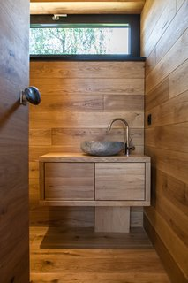 The wood-clad bathroom features a full shower and custom-made natural stone sink, which was created from a rock found at a neighboring river.