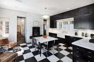 The gourmet, black-and-white kitchen houses the original fireplace, along with an eat-in area.