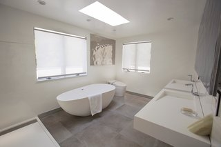 The master bath has a cool, neutral palette and a freestanding soaking tub.