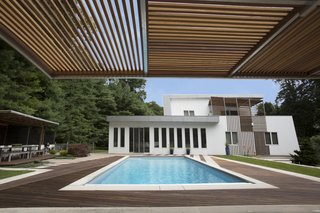 The backyard features a pristine pool and several alfresco entertaining areas shaded by cantilevering canopies.