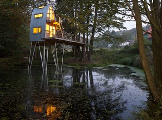 A stately group of hemlock trees on the shore of two ponds provided the perfect site for this enchanting, two-story structure located in Uslar, Germany. Designed for a client's young son, the tree house features a rounded steel facade with flanking wooden arches built from laminated wood.