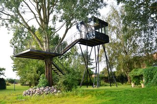 Perched on the German island of Usedom, this contemporary tree house is embedded in its context through a sleek, black-reflecting facade and offers a clear view of the surrounding lush landscape. The tree house rests independently on eight sloping steel columns, while the large terrace (which features an outdoor shower) is supported by rope suspensions.