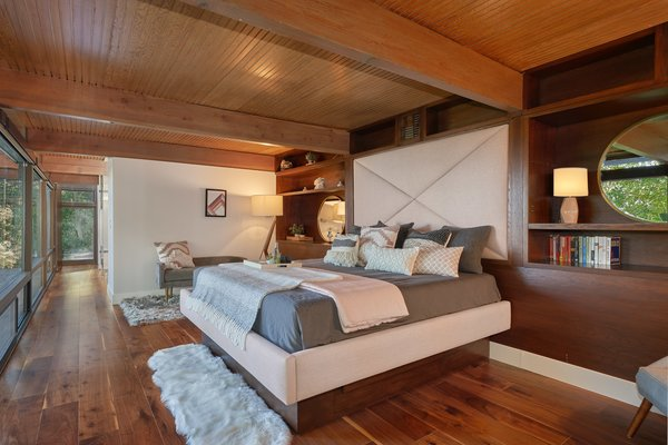 The master suite is a restful retreat, featuring an extensive window wall as well as beautifully restored hardwood and original paneling.