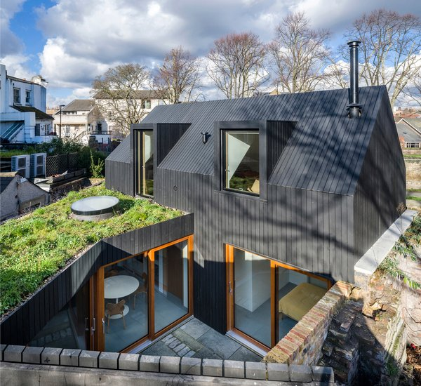 The black-stained wood siding of the Crossfield St House references London's timber-clad houses from the 17th and 18th centuries.