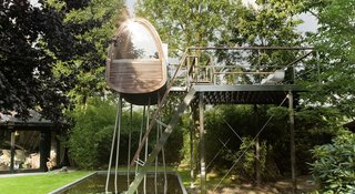 Surrounded by tall bamboo, the Frog Prince tree house floats above a shallow pond in a private garden in Münster, Germany.