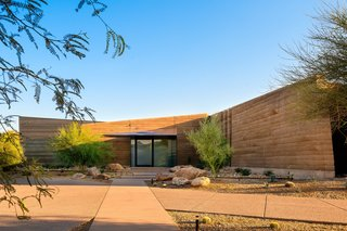 Layered, rammed-earth walls link Dancing Light House to its desert landscape.