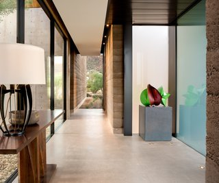 Inside, rammed-earth walls and cast-in-situ concrete are left exposed, strengthening the home's relationship to nature.