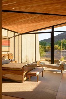 A bedroom features floor-to-ceiling windows, allowing the space to capture plenty of sunlight.