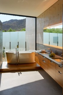 A floor-to-ceiling window in the bathroom frames mesmerizing mountain views.