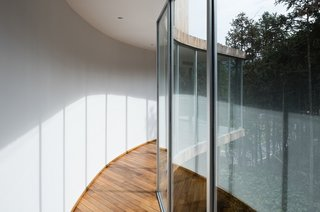Clean white walls and natural wood flooring redirect guests back toward the outside views.