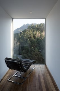 A minimalist reading room sits atop the structure and frames the lush mountain view.