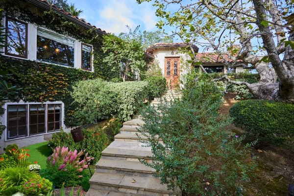 A lush landscape and ivy-covered entrance awaits prospective buyers.