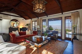 The main living area sits underneath dark wood beams and includes a wall of windows to take in the hillside views.