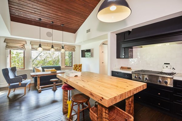 The kitchen features a large, butcher-block island, as well as vaulted, wood-paneled ceiling.
