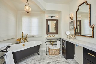 The marbled master bath offers a clawfoot soaking tub and black design accents throughout.