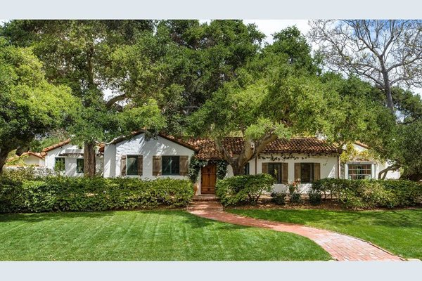 The Spanish Colonial Revival style is recognizable from this home's smooth stucco exterior, clay tiled roof, and other natural accents.
