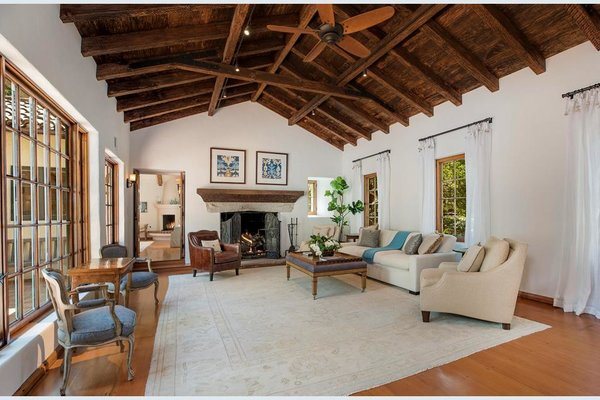 The Spanish style continues inside, with wood-beamed, vaulted ceilings in the living room.