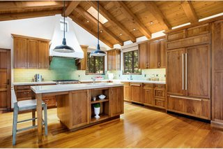 The newly remodeled kitchen features skylights and warm wooden cabinetry to complement the home's original style.