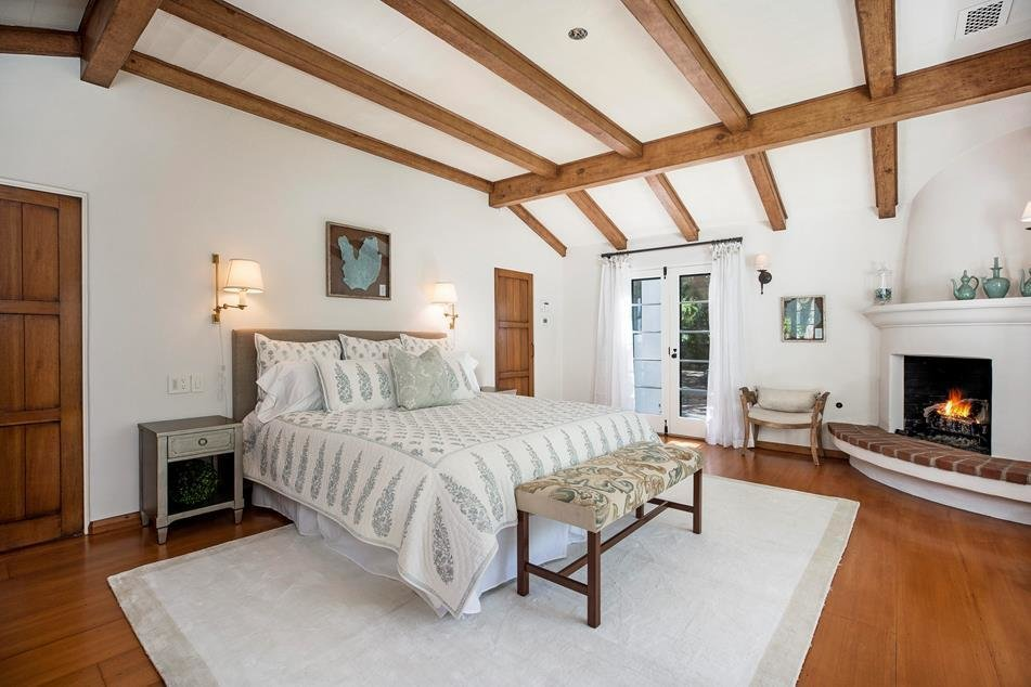 The master suite is finished in the same style of the rest of the home, and also offers a fireplace and French doors to the back patio.  Photo 6 of 10 in Actor Jeff Bridges Lists His Spanish Colonial Revival Abode For $8M