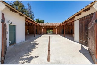 The large property also includes several detached structures, including a horse stable.