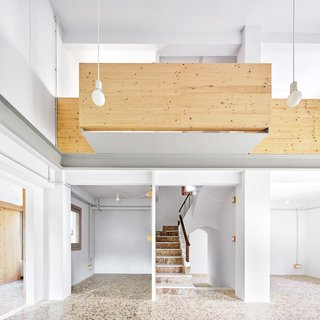 Since Josep and Encarna wanted to live on a single level, Tapias removed part of the mas's second floor to create a double-height space. Pendants by Faro Barcelona hang near the balcony Mas. The ground floor, designed to be flexible, currently holds offices for the couple, a library, a living room, and a piano for their teenage daughter. The terrazzo floors are original to the house.